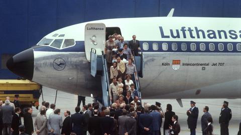 """Einige der befreiten Geiseln aus der """"Landshut"""", zum Teil in Decken gehüllt, kehren am 18. Oktober 1977 mit einer anderen Maschine auf den Flughafen Frankfurt zurück."""