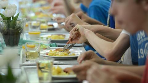 Schüler essen in der Mensa der Schule zusammen an einem langen Tisch.