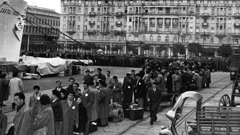 Auswanderer nach Australien warten 1953 im Hafen von Triest auf die Einschiffung.