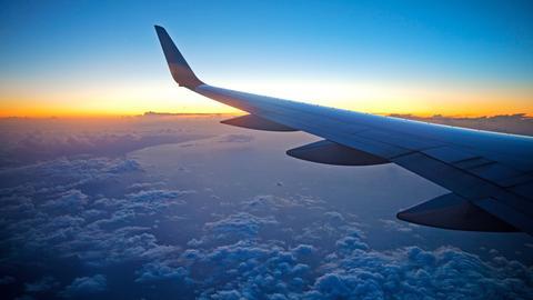 Blick aus dem Flugzeug auf eine Tragflaeche bei Sonnenaufgang ueber den Wolken