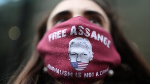 """Frau trägt eine Maske mit """"Free Assange"""""""