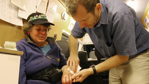 Gerhard Trabert versorgt die entzündete Hand einer obdachlosen Patientin in seinem Arztmobil in Mainz.