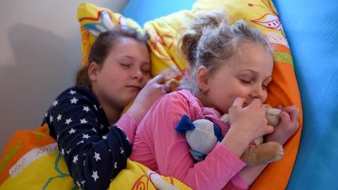 Die Schwestern Skady-Lee (10) und Lucy-Mae (6) liegen am 03.05.2016 in Flensburg (Schleswig-Holstein) in einem Bett der Nacht-Kita der Kindertagesstätte Kapernaum, dem Betriebskindergarten des Krankenhauses Diako.
