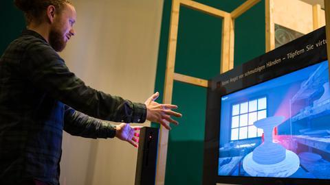 Ein Mann formt Gesten vor einem Bildschirm