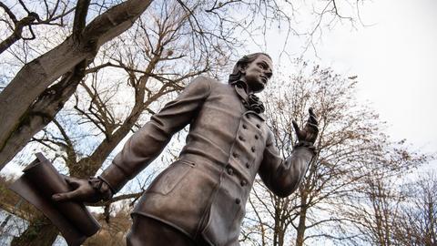 Eine Skulptur des Künstlers Waldemar Schröder, die Friedrich Hölderlin darstellt, steht vor Bäumen.