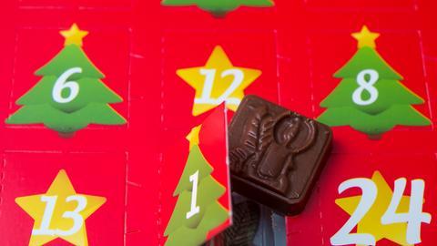 Ein kleines Schokoladenstück liegt neben dem ersten geöffneten Türchen eines Adventskalenders am 24.11.2015 in Sieversdorf (Brandenburg)