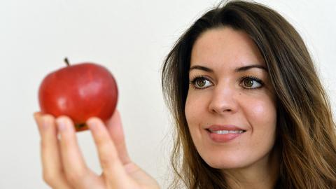 Eine junge Frau hält einen Apfel in der Hand.
