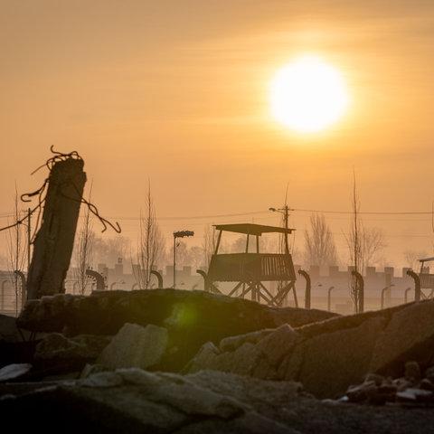 Die Sonne geht am frühen Morgen hinter der Ruine einer Gaskammer, den Stacheldrahtzäunen und Wachtürmen des früheren Vernichtungslagers Auschwitz-Birkenau auf.