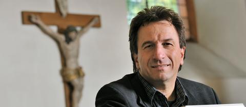 Der evangelische Pfarrer und Liedermacher Clemens Bittlinger sitzt auf einer Bank in der evangelischen Kirche in Ober-Ramstadt, im Hintergrund ist ein Kreuz zu sehen.