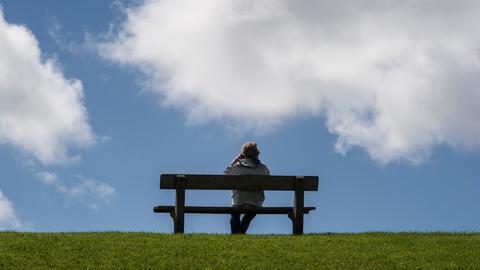 Eine Frau sitzt in Pellworm auf einer Bank auf dem Deich