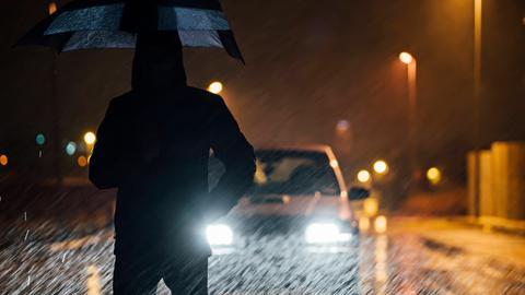 Mann steht bei Nacht im Regen vor Auto