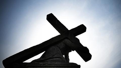 Unter blauem Himmel und gegen die Sonne zeichnet sich eine Jesusstatue unter dem Kreuz ab.