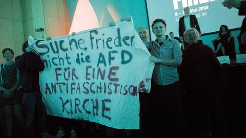 """junge Gläubige halten Transparent mit der Aufschrift """"Suche Frieden, nicht die AfD - für eine antifaschistische Kirche"""""""