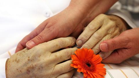 In einem Hospiz werden die Hände einer verstorbenen Frau gehalten.