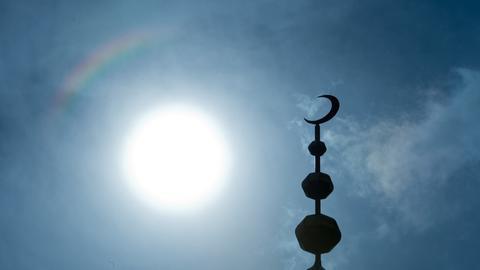 Der Halbmond auf dem Minarett der Abubakr Moschee hebt sich als Schattenriss vor der Sonne ab