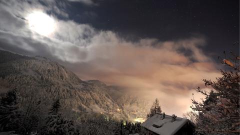 Der Mond geht über den Alpen auf.