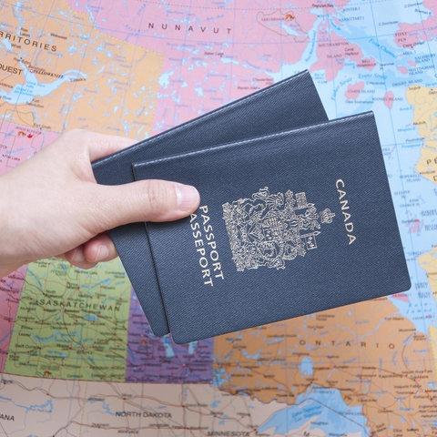 Hand hält zwei Personalausweise vor einer Weltkarte