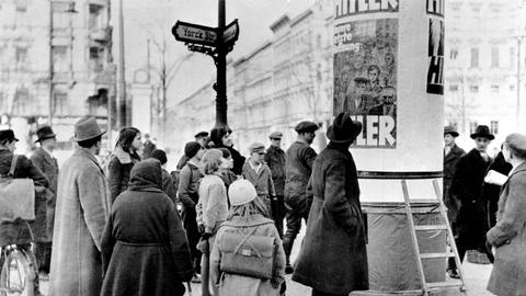 Berliner Passanten betrachten Wahlplakate zur Reichstagswahl im November 1932, bei der die NSDAP ein Drittel aller abgegebenen Stimmen errang.