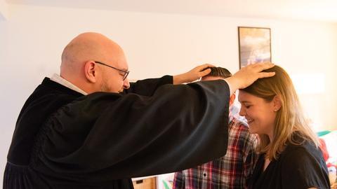 Pfarrer segnet ein Ehepaar bei einem Wohnzimmergottesdienst am Valentinstag