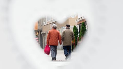 """Ein älteres Paar geht am Cafe """"Glücksmoment"""" vorbei, fotografiert durch einen Teelichthalter des Cafes in Herzchenform."""