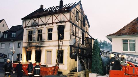 Feuerwehrmänner vor dem abgebrannten Haus der türkischen Familie Genc in Solingen