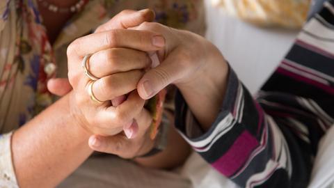 Eine Therapeutin hält am 09.09.2014 in einem Hospiz in Stuttgart (Baden-Württemberg) die Hand einer todkranken Bewohnerin.