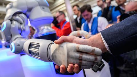 Ein Roboter gibt einem Mann die Hand