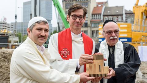 """Imam Kadir Sanci, Pfarrer Gregor Hohberg, Rabiner Andreas Nachama feiern den Abschluss der Tiefgründungsarbeiten für das """"House of One"""" in Berlin."""