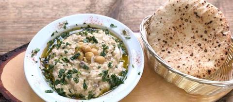Hummus mit einem Stück Pita auf einem Holzbrett