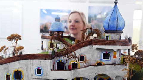 Eine Frau steht am 03.04.2014 in der Kunsthalle Messmer in Riegel (Baden-Württemberg) vor einem Modell der Kindertagesstätte Heddernheim des österreichischen Künstlers Friedensreich Hundertwasser.