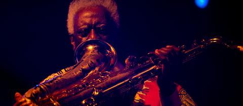 Pharoah Sanders spricht in den Schalltrichter seines Saxophons