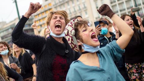 Frauen schreien bei einer Demonstration zum Frauentag in Athen