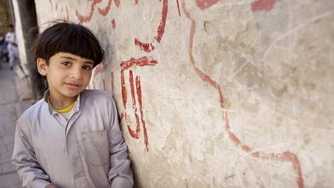 Junge steht vor Hauswand mit arabischer Schrift