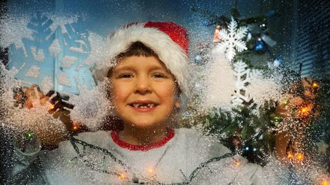 Junge am Fenster mit Schneeflocken