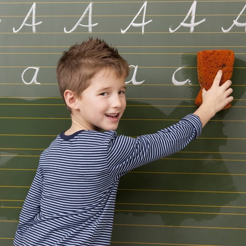 Junge wischt Buchstaben an Schultafel weg