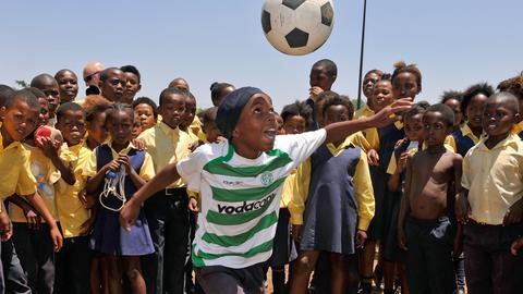 Kinder spielen in Südafrika Fußball.