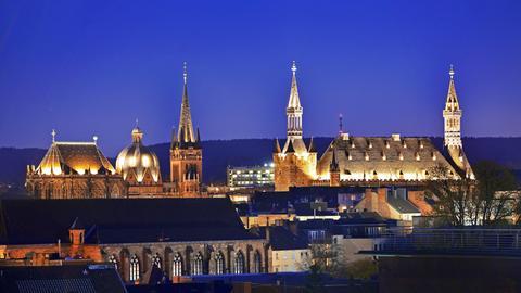 Die beleuchteten Türme von Aachener Dom und Rathaus schweben über den Dächern von Aachen.