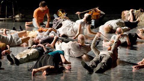 """Mitglieder des """"Ensemble Modern"""" liegen während des Festivals Frankfurter Positionen 2008 auf der Bühne."""