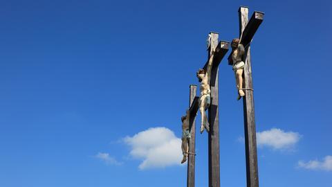 Drei Kreuze vor Wolkenhimmel