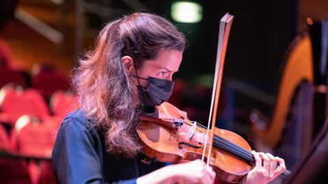 Musikerin spielt Geige mit Maske