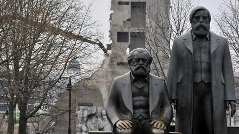 Das letzte Treppenhaus des Palastes der Republik wird 2008 in Berlin von einem Bagger abgerissen. Im Vordergrund sitzt die Bronzefigur von Karl Marx, daneben Friedrich Engels.