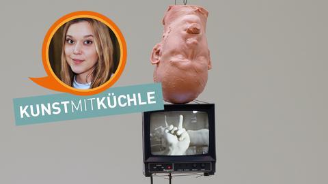 Installation von Bruce Nauman: Ein umgekehrter menschlicher Kopf aus Wachs hängt über einem Monitor, der eine Hand mit ausgestrecktem Mittelfinger zeigt.