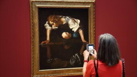 Kunstausstellung: Frau fotografiert Gemälde ab