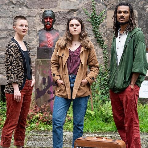 Drei junge Leute vor einer Bronze-Statue von Kolonialschul-gründer Fabarius