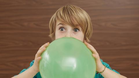 Junge pusten Luftballon