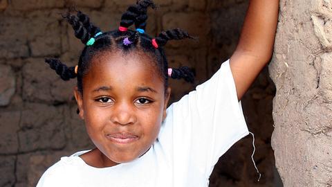 Kleines Mädchen steht im Eingang einer Lehmhütte.