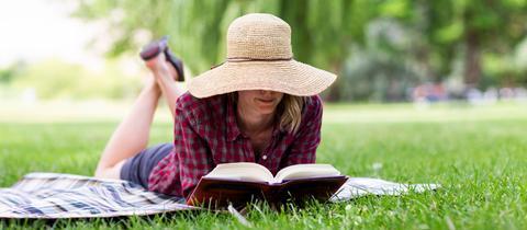 ine Frau liest ein Buch auf der Wiese - Frankfurt liest ein Buch