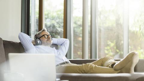 Mann liegt auf dem Sofa und hört Musik