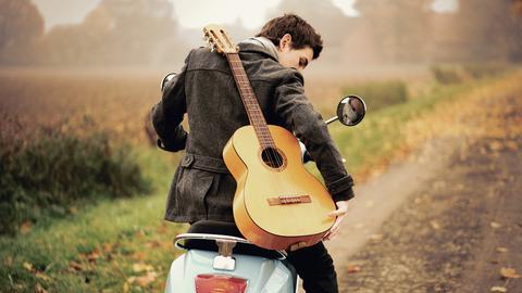Junger Mann mit umgehängter Gitarre auf einer Vespa
