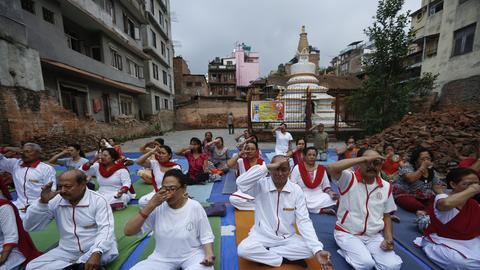 Yogis sitzen auf einem Platz und meditieren